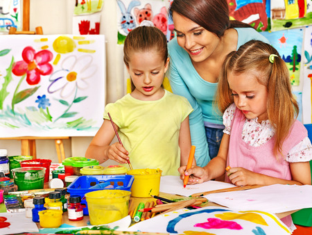 Happy children  with teacher painting. Banque d'images