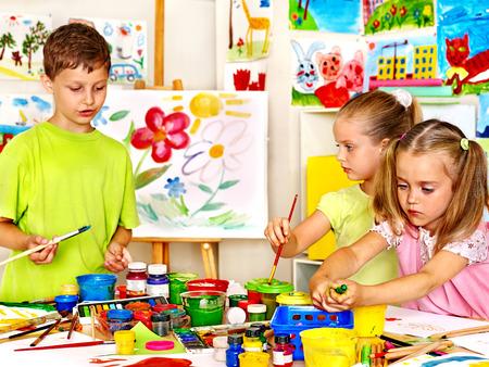 Kind schilderij op ezel op school. Leraar hulp.