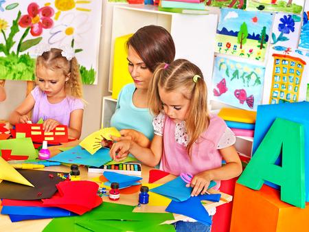 Children  cutting out scissors paper in preschool. photo