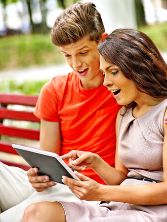 Couple with tablet pc sit on bench  . Outdoor. photo