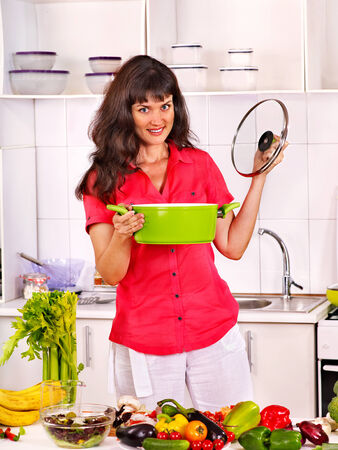 Happy woman cooking breakfast at kitchen. photo