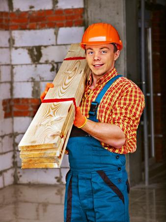 Happy man in builder uniform carry boards indoor. photo