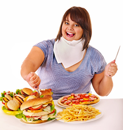 high calorie foods: Overweight woman eating fast food.
