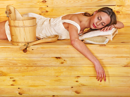 overheating: Young woman in sauna. Overheating danger.