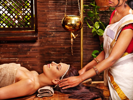 window treatments: Young woman having oil Ayurveda spa treatment. Stock Photo