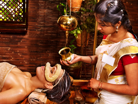 Woman having facial oil eyes mask at ayurveda spa.