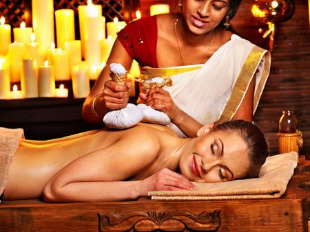 Femme ayant le massage ayurvédique avec une housse de riz.