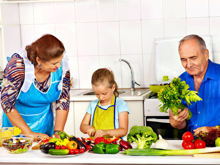 Family with child cooking at kitchen. Grandfather and grandmother. photo