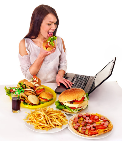 take out food: Woman eating fast food at work. Isolated. Stock Photo