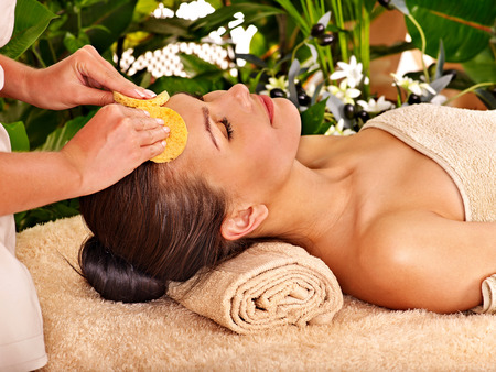 Woman getting facial massage in tropical beauty spa. Stock Photo
