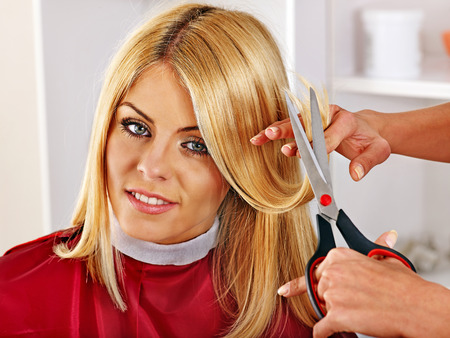 Woman at hairdresser with iron hair curler. photo