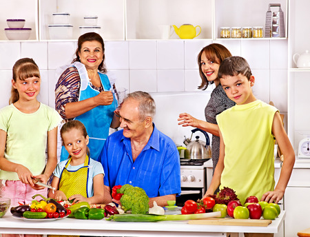 Happy family with child cooking at kitchen. Grandfather and grandmother. photo