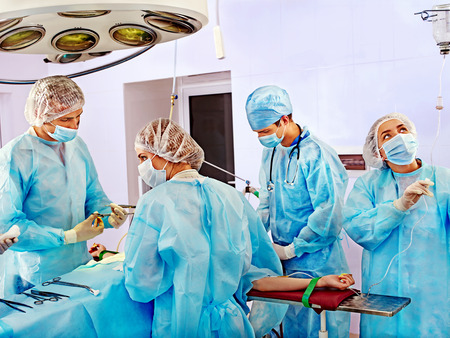 operating: Team surgeon at work in operating room.