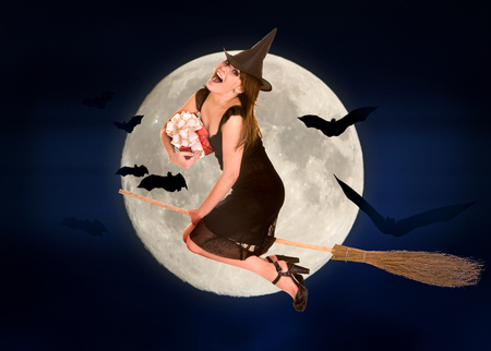 sabbath: Witch flying on broomstick with gift box. Halloween moon.