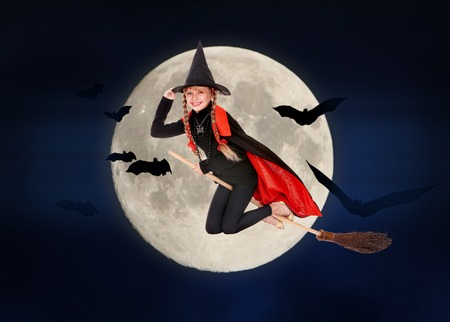 Kid witch flying on broomstick. Halloween moon. photo