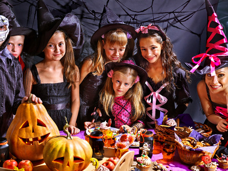 trick or treat: Children on Halloween party  sitting at trick or treat table. Stock Photo