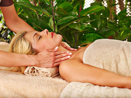 Woman getting facial massage in tropical spa. photo