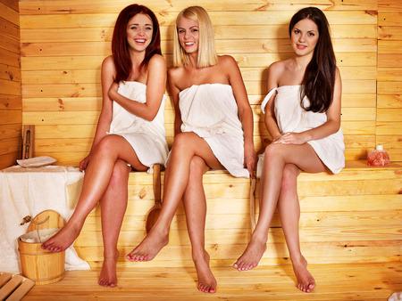 woman in towel: Group people relaxing in sauna.