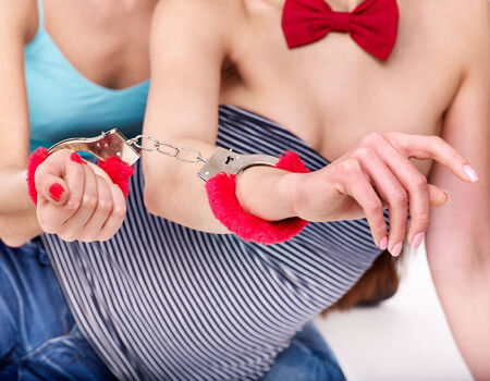 sex toys: Sexy lesbian women with handcuffs  in erotic game. Isolated. Stock Photo