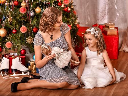 vistiendose: Niño con la madre que recibe los regalos bajo el árbol de Navidad. Foto de archivo