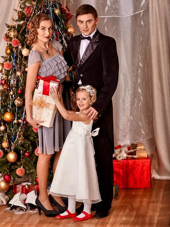 vistiendose: Familia feliz con los niños que viste el árbol de Navidad.