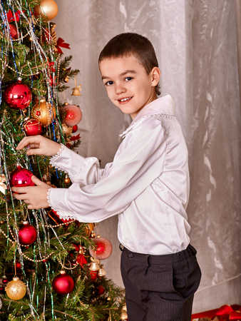 Happy child decorate on Christmas tree. photo