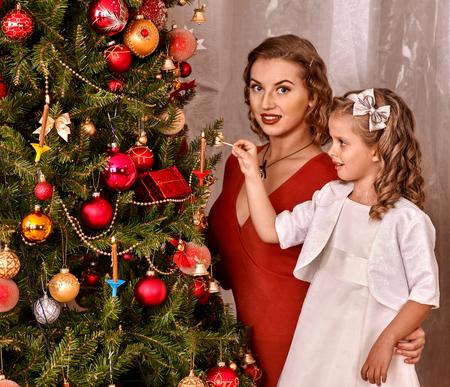 niños vistiendose: Familia feliz con los niños que viste el árbol de Navidad.