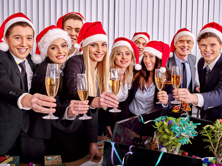 office party: Happy business group people in santa hat drinking champagne  Xmas