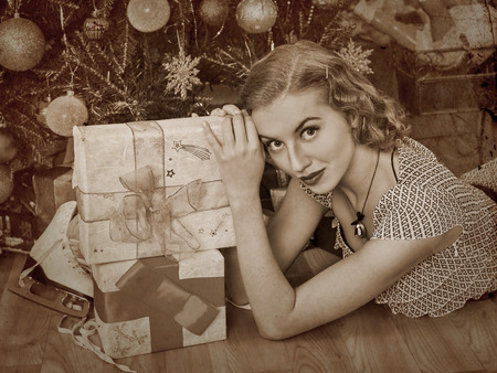 sepia toned: Woman receiving gifts under Christmas tree. Sepia toned. Stock Photo