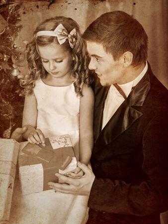 ni�os vistiendose: Ni�o con el padre que recibe cerca del �rbol de Navidad.