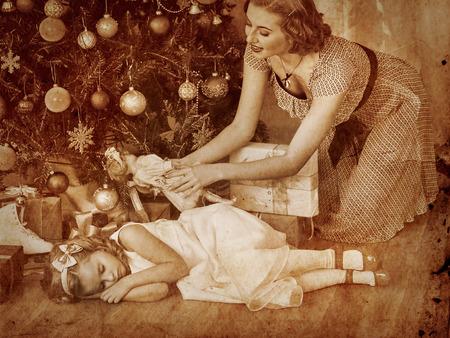 ni�os vistiendose: Ni�o con la madre que recibe cerca del �rbol de Navidad.