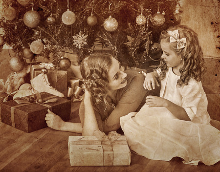 Child with mother receiving near Christmas tree. photo