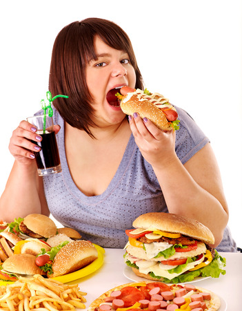 fat: Overweight woman eating fast food.