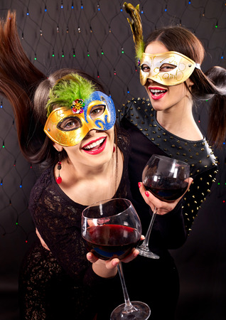 Lesbian women dancing with red wine.Black background. photo
