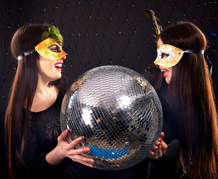Lesbian women in carnival mask with disco ball.Black background. photo