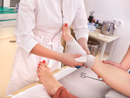 wound care: Doctor bandaging foot patient in hospital.