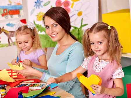 preschool: Happy children  with teacher painting. Stock Photo