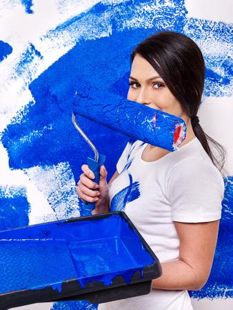 diy home repair: Happy woman paint wall at home.