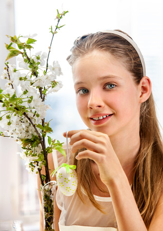 Happy beauty child hang easter egg on cherry branch. Window in background photo