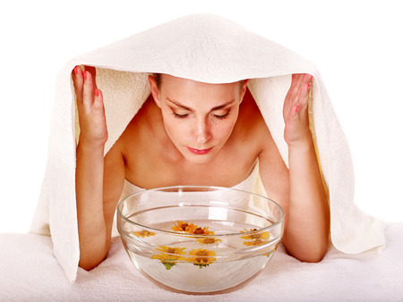 蒸気の治療と顔のマッサージ。頭の上のタオル
