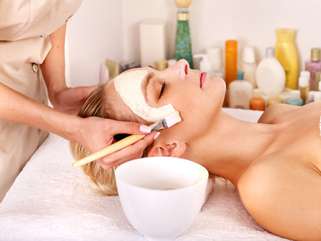 causing: Woman with clay facial mask in beauty spa, are only visible hands causing mask to face Stock Photo