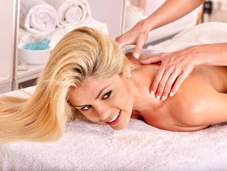 terrycloth: Blond woman getting massage in health resort. Lying on terrycloth