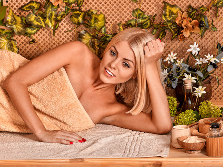 terrycloth: Woman getting back massage in tropical spa. Lying on beige terrycloth Stock Photo