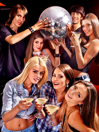 lighting effects musician: Group people  on disco in night club. Girls holding disco ball