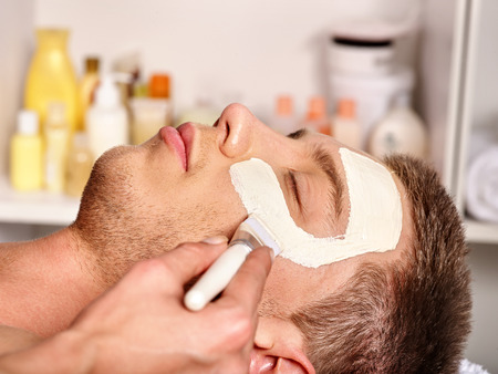 facial: Man with clay facial mask in beauty spa. Male face close up. Stock Photo