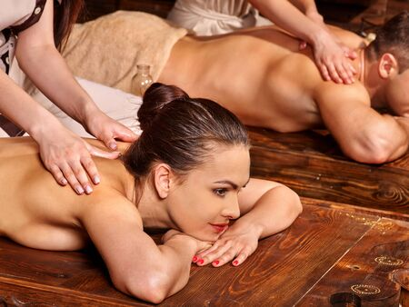 aromatherapy oil: Couple  having oil Ayurveda spa treatment. Couple lying on dark boards.