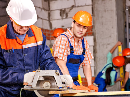 circular saw: Happy group people  builder with circular saw. Brick wall in the background