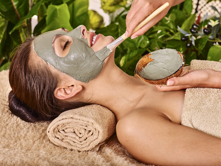 female beauty: Woman with clay facial mask in beauty spa. In background tropical plants