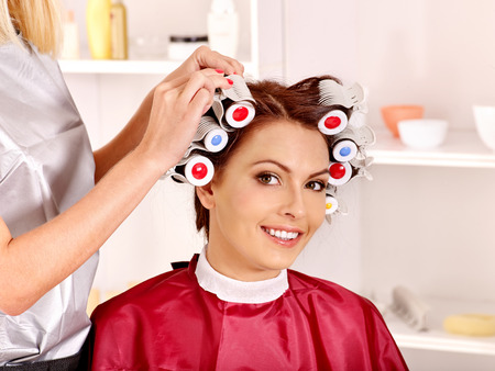 hot rollers: Happy woman wear hair curlers on head. Barber is in  barbershop Stock Photo