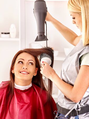 hairdryer: Woman at hairdresser with hairdryer. Barber  is in hair salon with a client Stock Photo